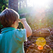 Child standing in sunlit forest | © The State of Queensland